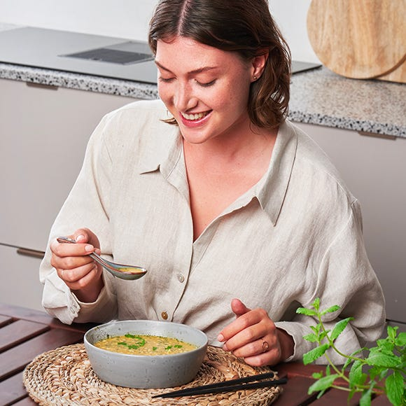 Een vrouw geniet van een MODIFAST soep